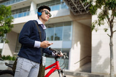Young man with bicycle. Young Asian man in headphones standing with his bicycle Stock Images