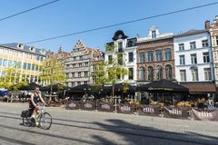 Young man on bicycle circulating in Ghent, Belgium. Ghent, Belgium - August 29, 2017: Young man on bicycle circulating and people walking in an old historic Royalty Free Stock Photo