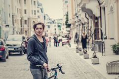 Young man with a bicycle on a city street Stock Photo