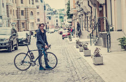 Young man with a bicycle on a city street Stock Image