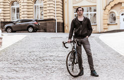 Young man with a bicycle on a city street Royalty Free Stock Photos