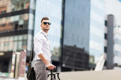 Young man with bicycle on city street Stock Images