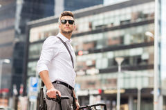 Young man with bicycle on city street Royalty Free Stock Photography