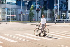 Young man with bicycle on crosswalk in city Stock Photo