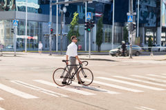 Young man with bicycle on crosswalk in city Royalty Free Stock Photos