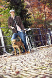 Young man with bicycle and dog. Young man with a bicycle and dog on the fence Royalty Free Stock Photos
