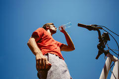 Young man on a bicycle drink water from below shot Stock Image