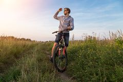 Young man on bicycle in field with green grass and flowers, beautiful nature landscape, copy space. Young man on bicycle, cyclist in field with green grass and royalty free stock photos