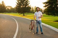 Young man with bicycle gesturing thumb up. Attractive stylish cyclist giving thumb up sign standing with bicycle on country road Stock Images