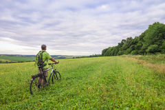 Young man with a bicycle on green field on a sunny summer day Stock Photos