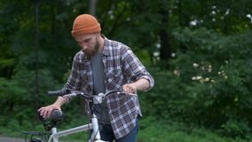 Young man with bicycle having outdoor fun. retro vintage style image. Happy hipster guy smile while riding bike on the stock video