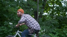 Young man with bicycle having outdoor fun. retro vintage style image. Happy hipster guy smile while riding bike on the stock video footage