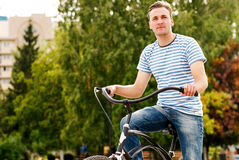 A young man on a bicycle looks into the distance Royalty Free Stock Photos