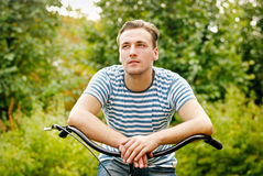 A young man on a bicycle looks into the distance Royalty Free Stock Photography