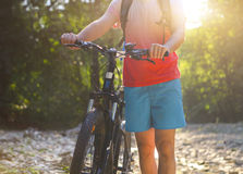Young man with bicycle by mountain river. Closeup Stock Images