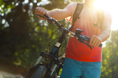 Young man with bicycle by mountain river. Closeup Royalty Free Stock Photography