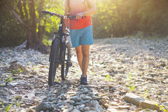 Young man with bicycle by mountain river. Closeup Stock Image