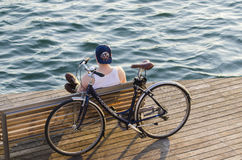A young man with a bicycle rests. BARCELONA, SPAIN - OCTOBER 6, 2014: A young man with a bicycle rests on one of the terraces overlooking the sea, in the Stock Image