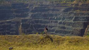 A young man on a Bicycle rides along the cliff of the canyon.  stock video footage