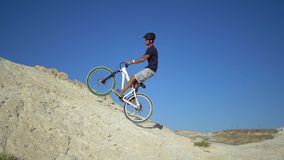 A young man on a bicycle rides from a mountain and jumps on a hillock. Slow motion stock video footage