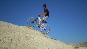 A young man on a bicycle rides from a mountain and jumps on a hillock. Slow motion stock footage