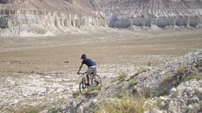 A young man on a bicycle is rolling from the mountain. Slow motion stock footage