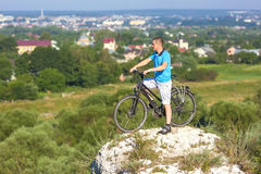Young man with a bicycle on a rock looking on a city Royalty Free Stock Photography