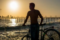 Young man with a bicycle standing on the beach at the sunset. Stock Photos