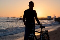 Young man with a bicycle standing on the beach at the sunset. Stock Images