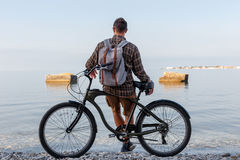 Young Man With Bicycle Standing On Coast And enjoying View Of Sea. Holiday Travel Activity Concept Royalty Free Stock Image