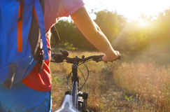 Young man with bicycle in the summer field. Royalty Free Stock Image