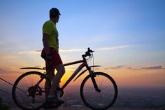 A young man with a bicycle at sunset. Stock Photos