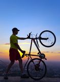 A young man with a bicycle at sunset. Royalty Free Stock Photography