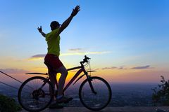A young man with a bicycle at sunset. Stock Photo
