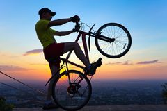A young man with a bicycle at sunset. Royalty Free Stock Photos