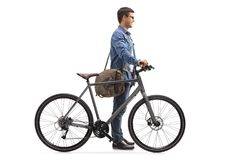 Young man with a bicycle waiting in line. Full length profile shot of a young man with a bicycle waiting in line isolated on white background Stock Images