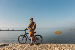 Young Man With Bicycle Walking On Coast And enjoying View Of Sea. Holiday Travel Activity Concept. Young traveler man with a backpack in sunglasses walking on Stock Photography