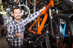 Young man in bicycles shop Stock Images