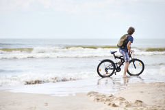 Young man bicycling along a beach Royalty Free Stock Photos