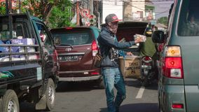A young man with a big box walks between cars on a busy street of Denpasar and sells traditional food. stock video footage