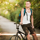 Young man on bike. Young man sitting on bike Stock Photo