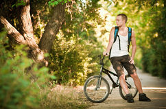 Young man on bike. Young man sitting on bike Royalty Free Stock Photos