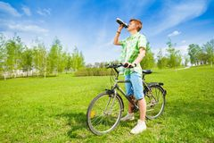 Young man on a bike drinking water Stock Photos