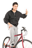 Young man on a bike giving a thumb up Royalty Free Stock Photos