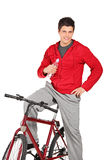 Young man on a bike holding water bottle Stock Images