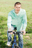 Young man on bike outdoors Stock Images
