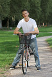 Young man with a bike in a park Royalty Free Stock Photo