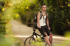 Young man on bike. Young man sitting on bike Royalty Free Stock Image