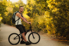 Young man on bike. Young man sitting on bike Stock Images