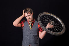 Young man with bike wheel Stock Image